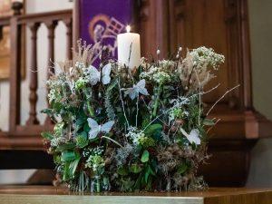 Kerststuk in de Joriskerk. Bovenin staat een brandende witte kaars. De kaars staat op een 'rietschoof' versierd met hulst, eucalyptus, wit bloeiende bloemen en witte vlinders.